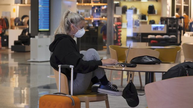 Girl in a Protective Mask Works on a Laptop in the Airport thumbnail