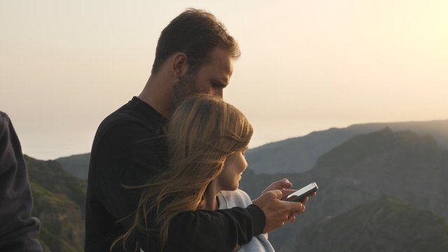 Couple Hugging & Looking on Phone  thumbnail