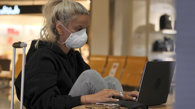 Girl Works and Waits for Flight in the Waiting Room thumbnail