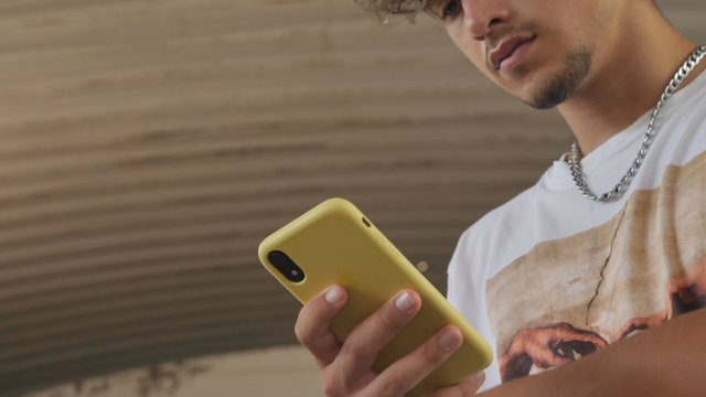 Guy Clicks in a Smartphone With a Yellow Case thumbnail