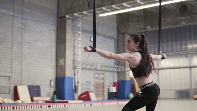 Young Athletic Woman Jumping On Straps And Spinning  thumbnail