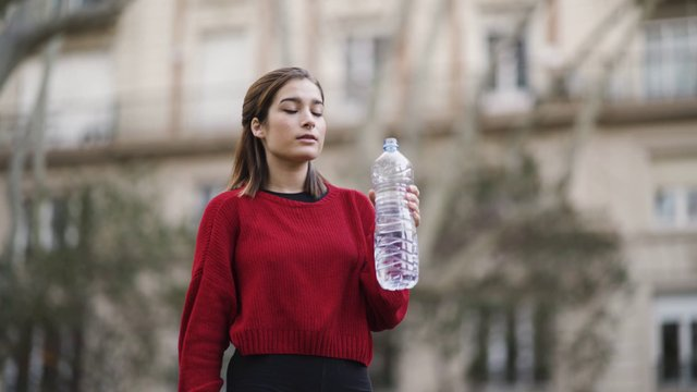 Girl Drinking Water In The Park thumbnail