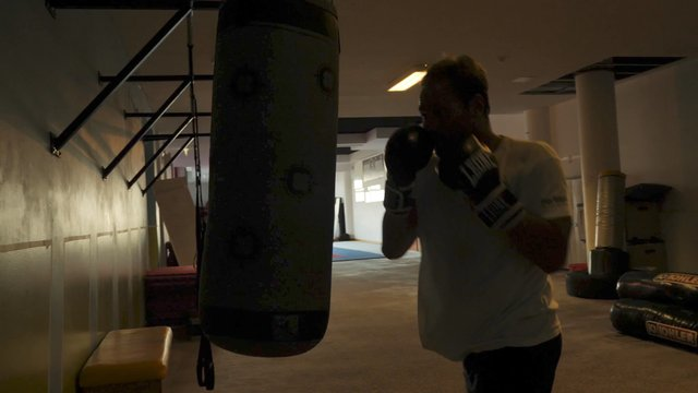 Boxer Hits a Punching Bag in the Dark Gym thumbnail