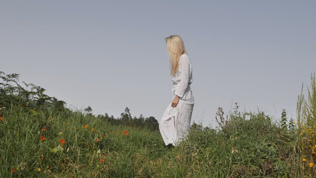 Girl Walking in Grass Field with Cowboy Boots thumbnail