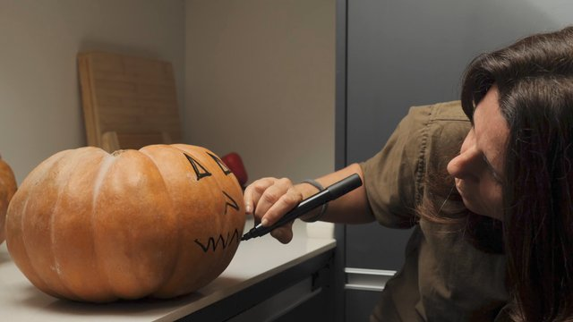 Close up of Woman Paints a Mouth on a Pumpkin thumbnail