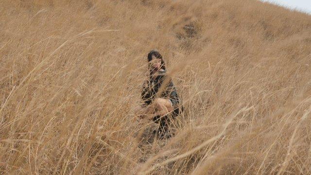 The Girl Poses Among Long Beige Grass thumbnail