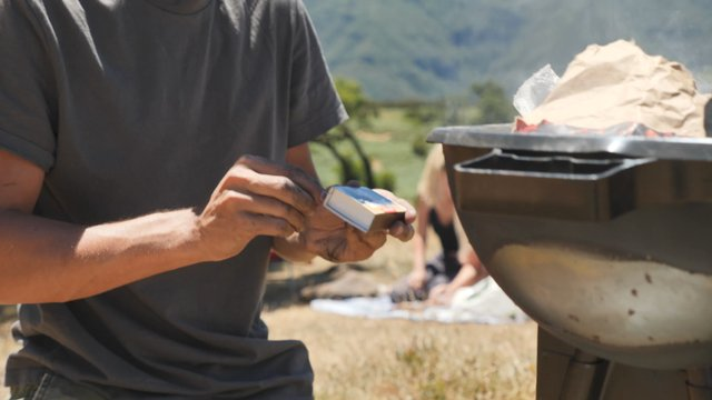 Young Man Lights a Barbecue Grill thumbnail