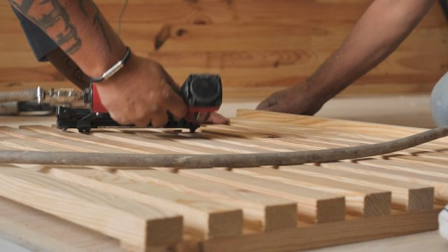 Male's Hands Drive Heavy Staples Into a Wood Board thumbnail