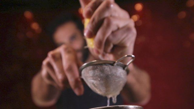 Bartender Squeezing Lemon Juice into Cocktail Shaker thumbnail
