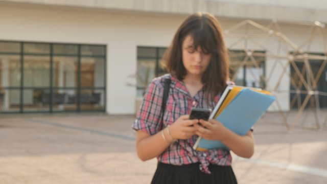 Girl Texting on School Campus thumbnail