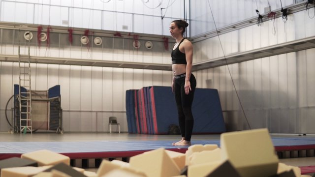 Woman Doing A Back Flip In The Gym thumbnail