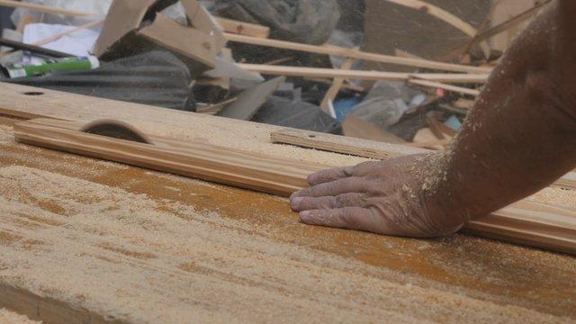A Carpenter Saws a Long Wood Plank thumbnail
