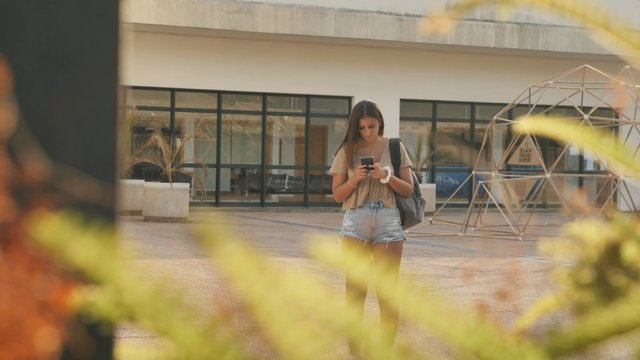 Brunette Girl Texting on School Campus thumbnail