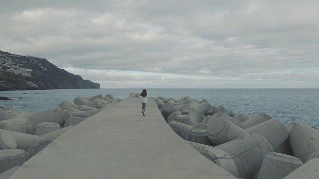 Young Girl Running near the Ocean thumbnail