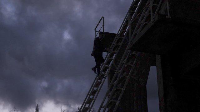 A Man in a Black Suit Climbs Down a Ladder thumbnail
