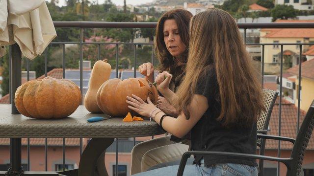 Young Girl Carves an Eye on a Pumpkin on the Balcony thumbnail