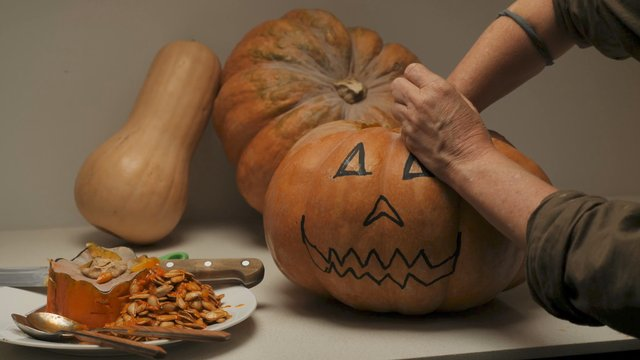 A Woman Pulls Out the Middle of a Pumpkin by Her Hands thumbnail