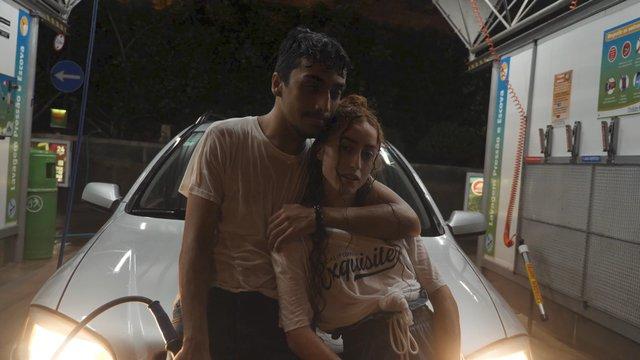 A Hugging Couple Lean on a Car thumbnail