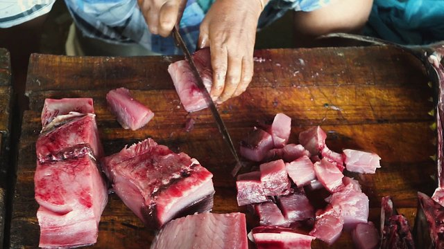 Top View Point Woman Cutting Tuna At The Fish Market In India thumbnail