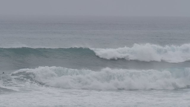 Surfers Paddling in Cloudy Weather thumbnail