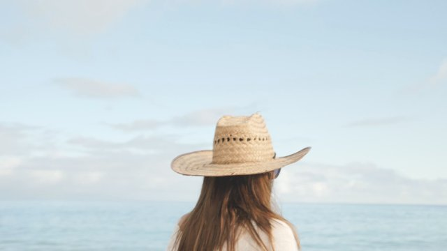 Lady in a Strawy Hat Walks Against Natural Blue Background thumbnail
