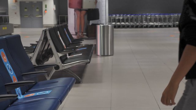 Girl Comes and Sits on the Bench at the Empty Terminal Lounge thumbnail