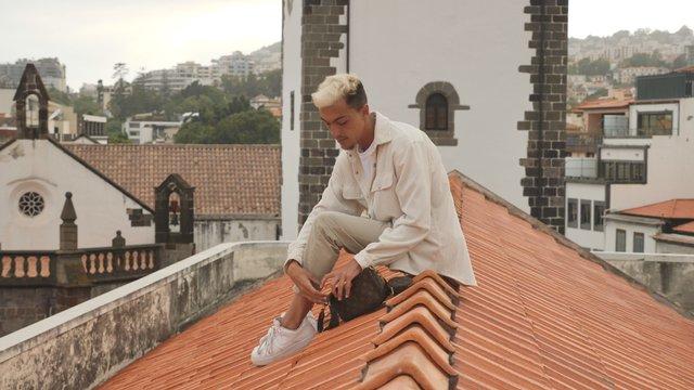 Young Man Checks his Bag on Rooftop thumbnail