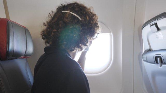 A Guy Closes an Airplane Window thumbnail