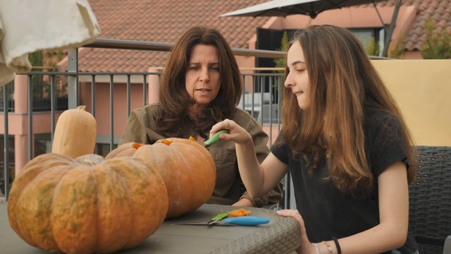 Young Girl Carves an Eye on a Pumpkin Outdoors thumbnail