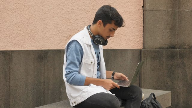 Black-Haired Guy Uses Laptop Outdoors thumbnail