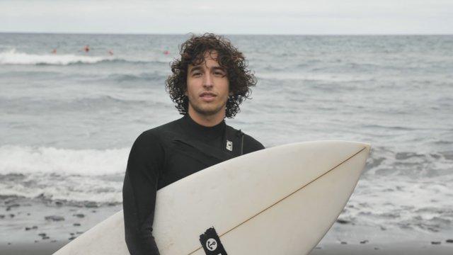 Smiling Surfer Boy on a Cloudy Beach thumbnail