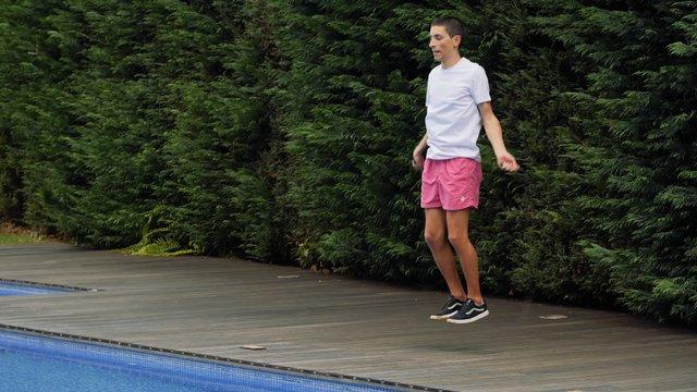 Boy Doing Jumping Rope Workout In Garden thumbnail