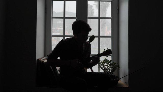 Playing the ukulele near the window