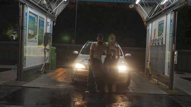 Girl and Guy Lean on a Car and Look at the Camera thumbnail