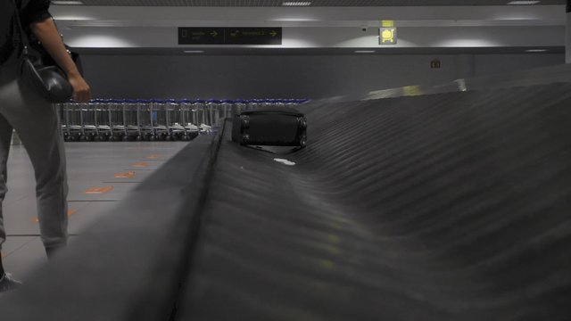 Side View of a Girl Takes a Suitcase From a Luggage Carousel thumbnail