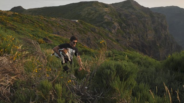 Man Running with a Dog on Mountain Top thumbnail