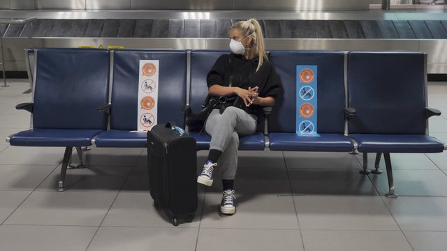 Woman Sits on the Airport During Pandemic thumbnail