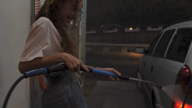 Girl Washes a Car With a Jet of High-Pressure Water thumbnail