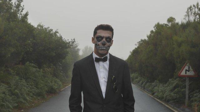 A Man With Skull Makeup Looks at the Camera thumbnail