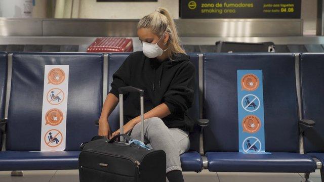 Pretty Girl Uses Phone at Airport Sitting at Terminal Lounge. thumbnail