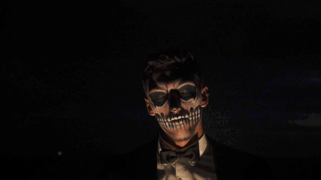 Halloween Man Stands in the Darkness and Looks at the Camera thumbnail
