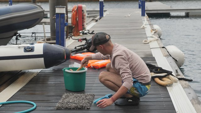 Young Man Cleaning a Rug on Dock  thumbnail
