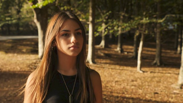 Young Girl With Hazel Eyes Walks in a Forest thumbnail