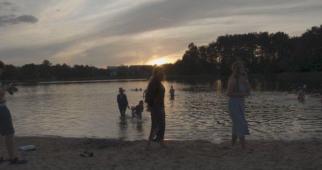 People Enjoying Golden Hour at Salote Lake in Vilnius  thumbnail