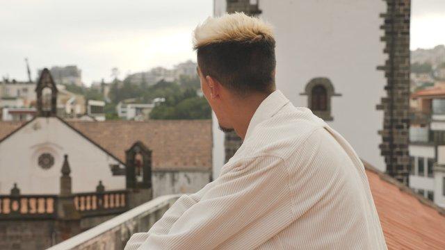 Young Man Enjoying Rooftop Sunset thumbnail