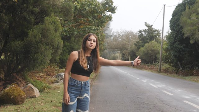Brunette Girl Hitchhiking on the Road thumbnail