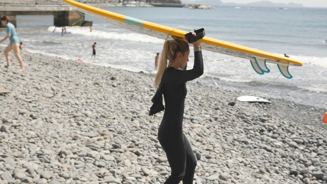 A Girl Carries a Surfboard Over the Head thumbnail