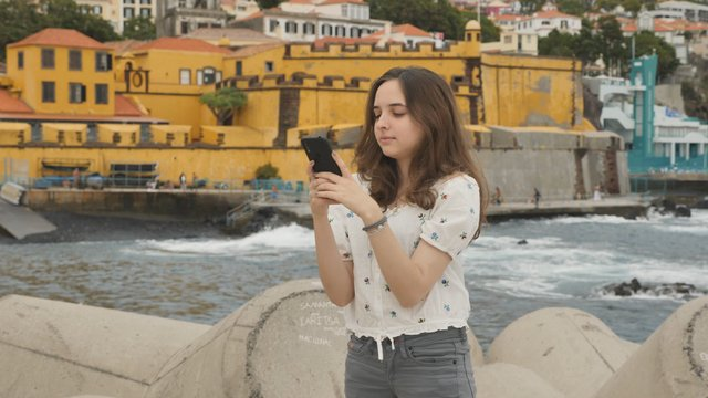 Happy Young Girl Texting near the Sea thumbnail