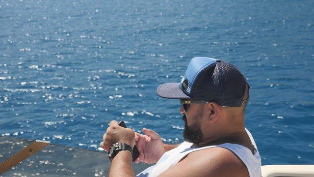 Man Texting on a Boat  thumbnail