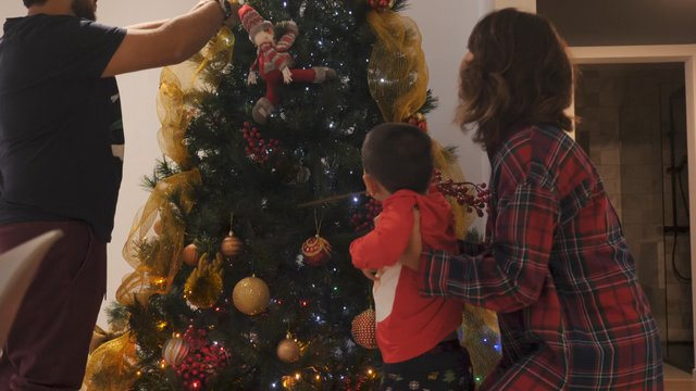 Happy Family Decorates Christmas Tree With Beautiful Ornaments And Baubles thumbnail